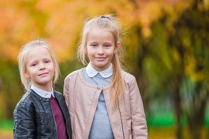 Little adorable girls outdoors at autumn day