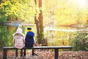 Two kids sitting on bench in forest
