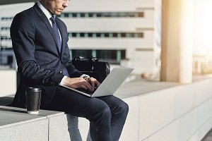 Man wearing suit while typing on laptop