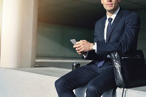 Man wearing suit holding a gray cellphone