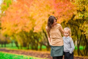 Family in fall. Mother and kid enjoy warm autumn