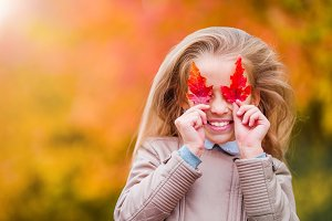 Portrait of adorable little girl with yellow and orange leaves outdoors at beautiful autumn day