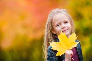 Portrait of adorable little girl with yellow leaves at beautiful autumn day