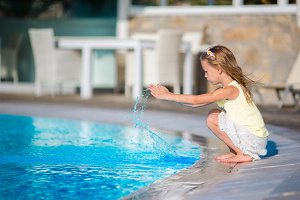 Cute little girl having fun with a splash near swimming pool