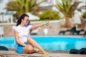 Young beautiful woman taking selfie on the edge of swimming pool