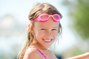 Smiling happy girl in goggles for swimming at outdoor pool