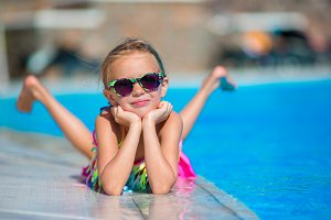 Little happy girl in outdoor swimming pool enjoy her vacation