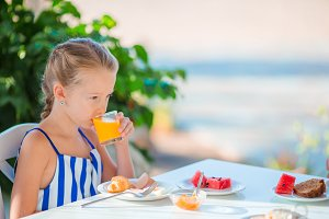 Adorable little girl drinking orange juice on breakfast with sea view