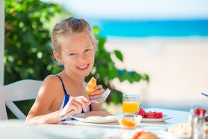 Adorable little girl having breakfast at cafe with sea view