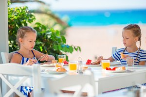 Lunch time. Little girls having breakfast at outdoor cafe with sea view
