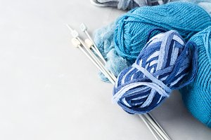 Blue woolen yarn with knitting needles on gray background