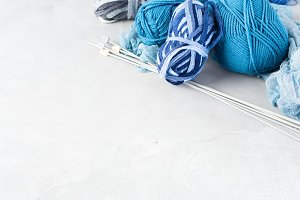 Background with blue yarn and knitting needles