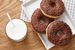 Glass of milk and chocolate donuts on wooden table