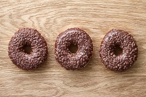 Three chocolate donuts on wooden rustic table