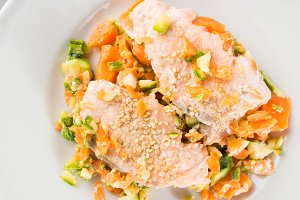 Steamed salmon with carrots and zucchini. Closeup