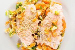 Steamed salmon with vegetables on white. Vertical