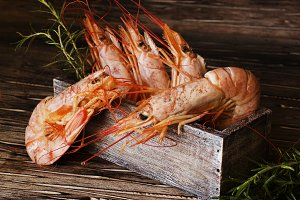 raw or cooked shrimp with rosemary in a wooden box