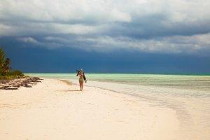 Lady walks on sandy beach Cuba
