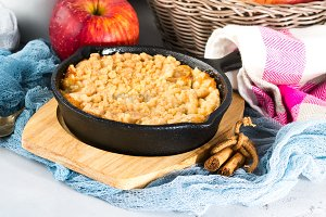 Home made apple crumble in cast iron skillet. Vertical