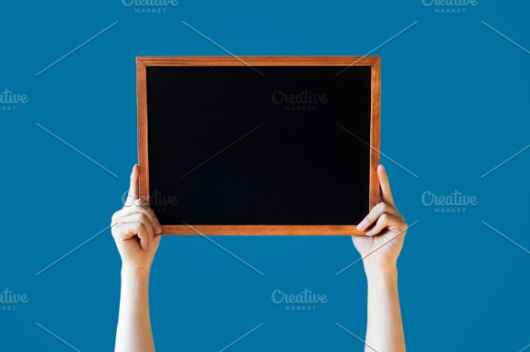 Human Hands Holding Empty Blank Black Board Over Blue Background - Ready for adding your text here