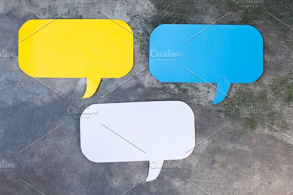 Three of Yellow, Blue and White Speech Bubbles Over Gray Grunge Background - Balloon speech bubble concept