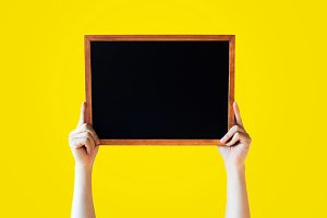 Human Hands Holding Empty Blank Black Board Over Yellow Background - Ready for adding your text here