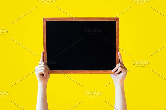 Human Hands Holding Empty Blank Black Board Over Yellow Background - Ready for adding your text here in Objects