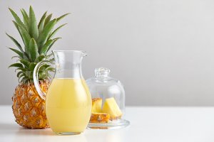 Glass jug with pineapple juice and fruit on table