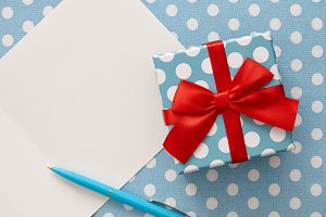 Polka dot gift box, blue pen and greeting card