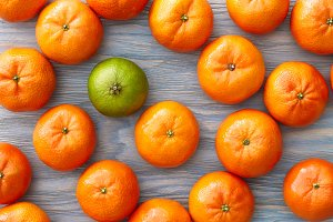 Lime and mandarines on blue background