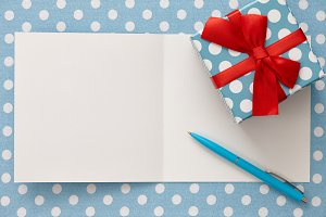 Greeting card with polka dot gift box and a pen