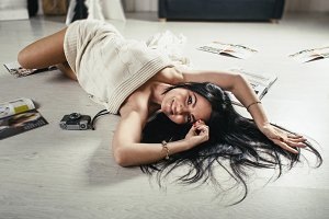 Warm toned picture of curvy sexy young brunette woman lying on floor among the glamorous magazines.