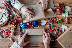 Hands wrapping Christmas gifts