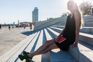 Blonde woman sitting on steps in BCN