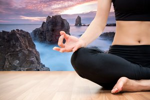 woman meditating on a wood floor