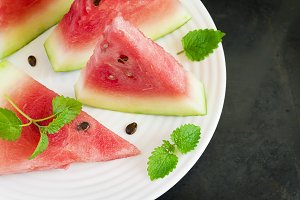 Slices of watermelon on a white plate, top view