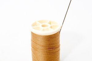 Spool of brown thread and needle