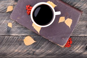 Coffee cup, old book, autumn leaves