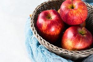 Red apples in basket on napkins. Healthy eating. Vertical