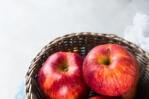 Gray background with fresh apples in basket