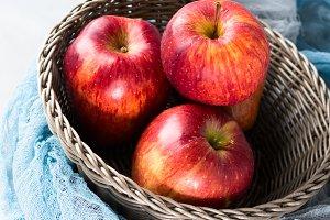 Fresh red apples in basket. Vertical. Healthy eating