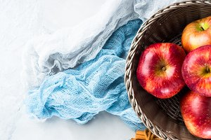 Fresh apples in basket on napkins. Autumn winter fruit