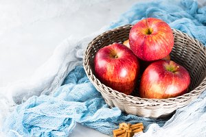 Fresh apples in basket on napkins and cinnamon