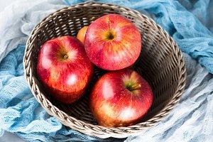 Fresh apples in basket on napkins