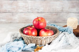 Fresh apples in basket on rustic background