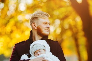 dad and newborn son in autumn park