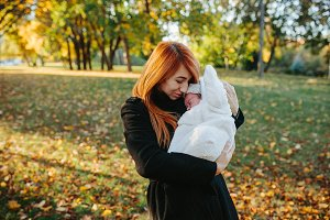 Mother and newborn son in autumn park