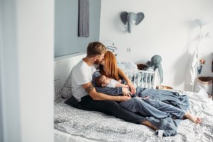 Happy family with newborn baby on the bed