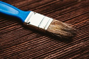 brush to paint on a dark wooden background