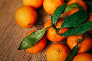 many fresh tangerines on a wooden background